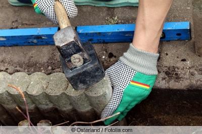 Mann schlägt Steine per Hammer ein
