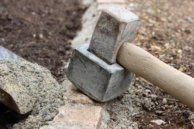 Rasenkantsteine mit Hammer einschlagen