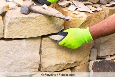Mann arbeitet an trockener Natursteinmauer