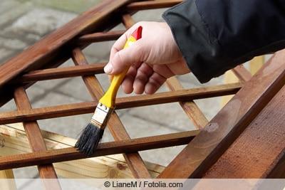 Streichen eines Holzspaliers