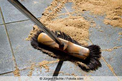 Steine reinigen mit Besen und Sand