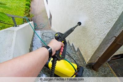 Hochdruckreiniger sprüht an Hauswand