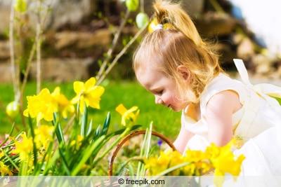 Kind mit Narzissen im Garten
