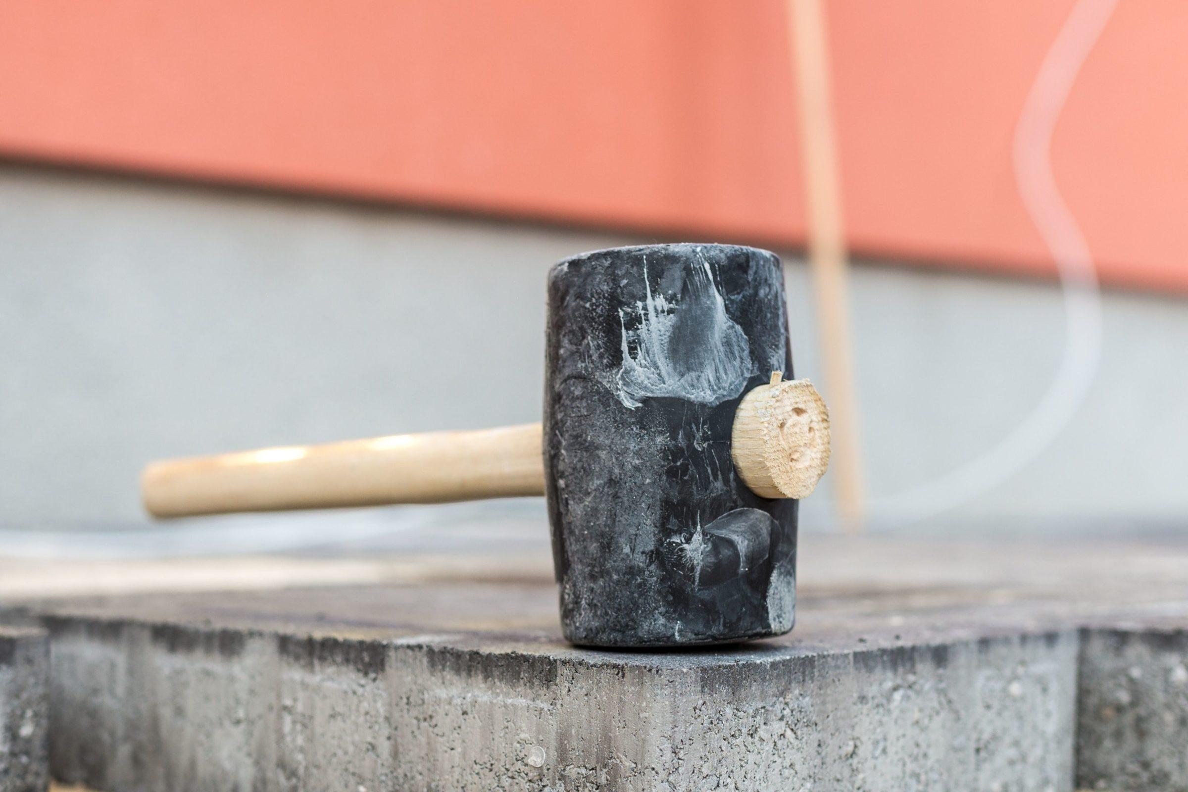 Trockene Zementflecken auf Pflaster mit Hammer abklopfen