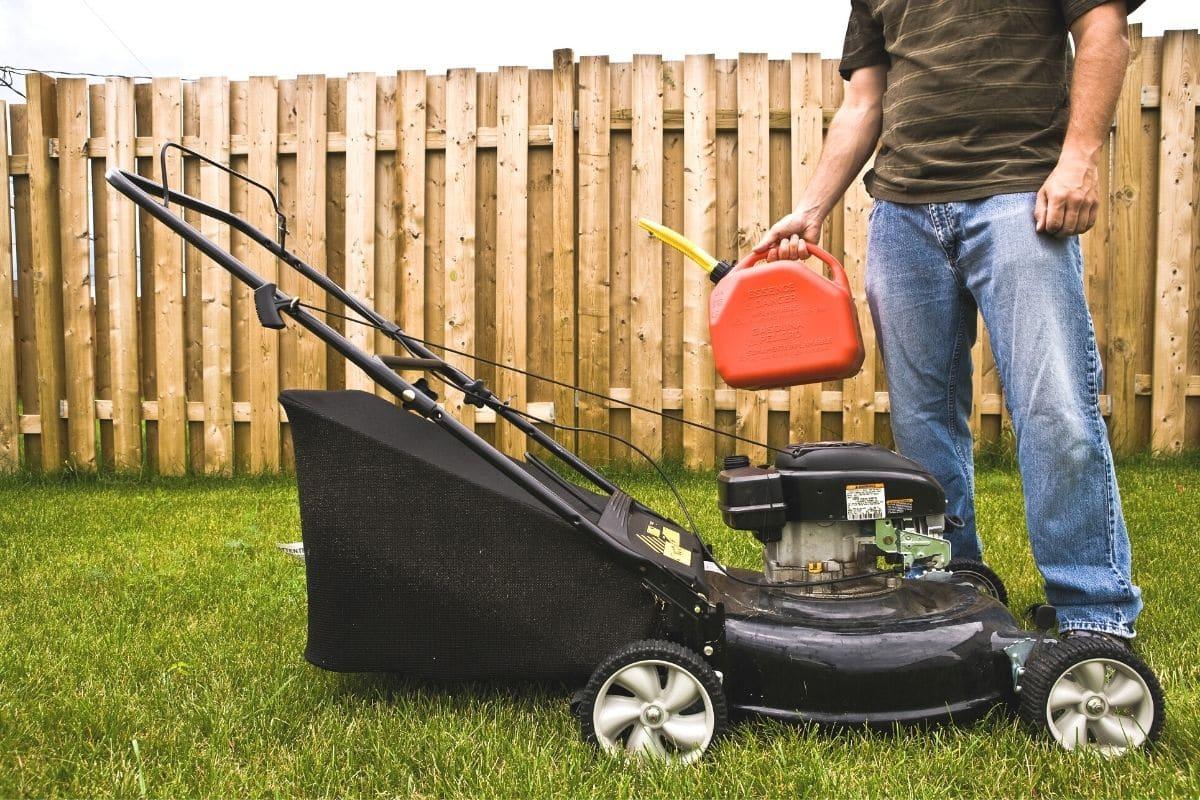 Rasenmäher-Antrieb reparieren - Mann füllt Treibstoff nach