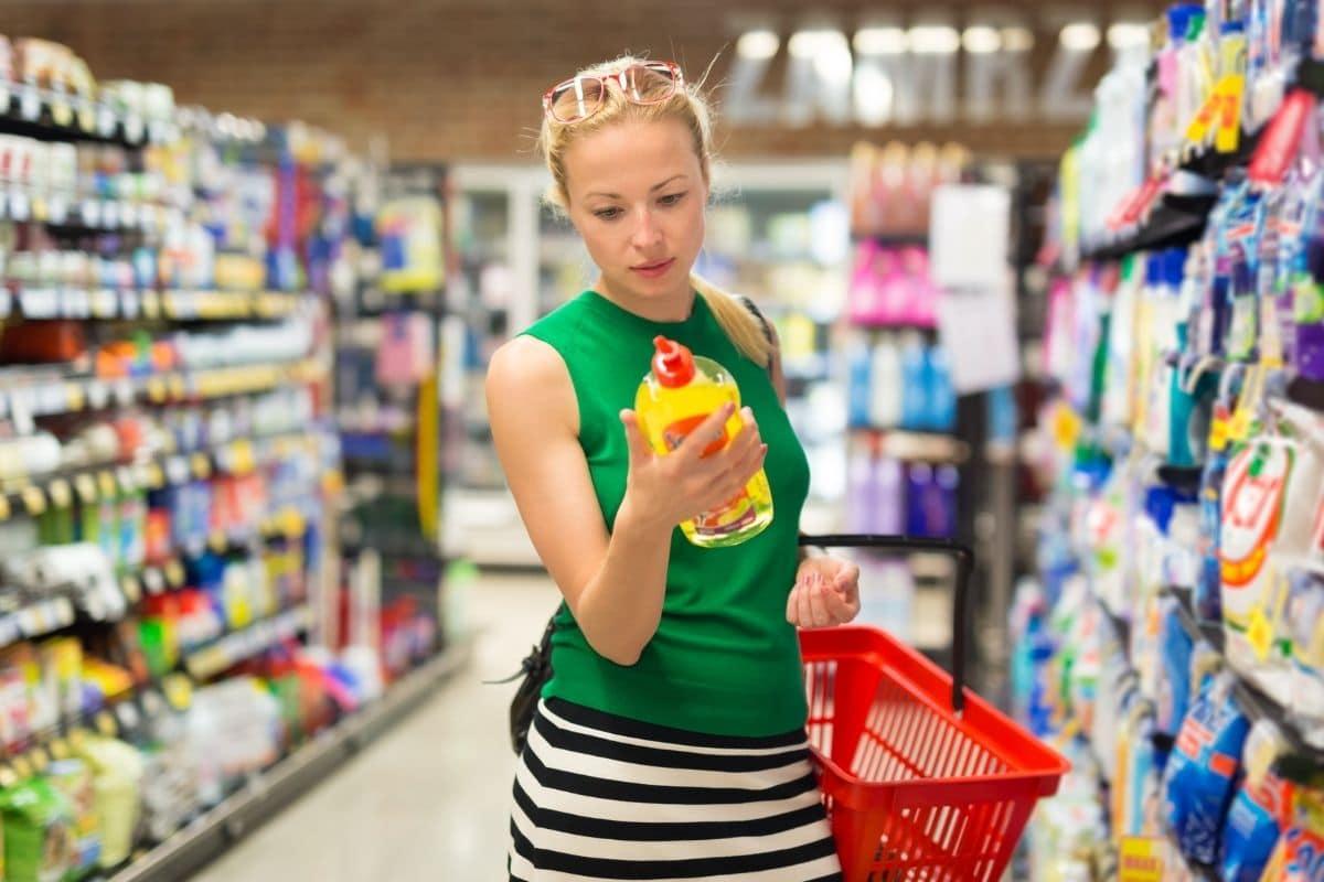 Haushaltsabteilung im Supermarkt - Frau schaut nach Essigreiniger