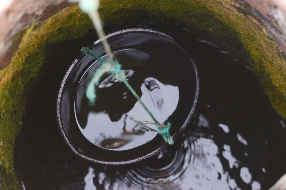 Brunnenwasser mit Eimer fördern