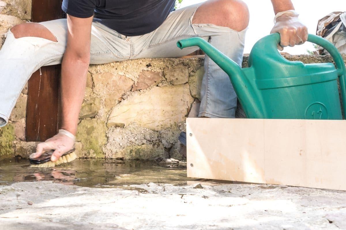 Ausblühungen im Beton mit Bürste und Wasser entfernen