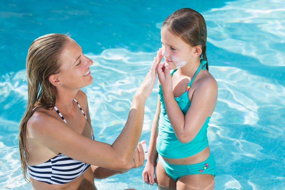Mutter schmiert Tochter im Pool mit Sonnencreme ein