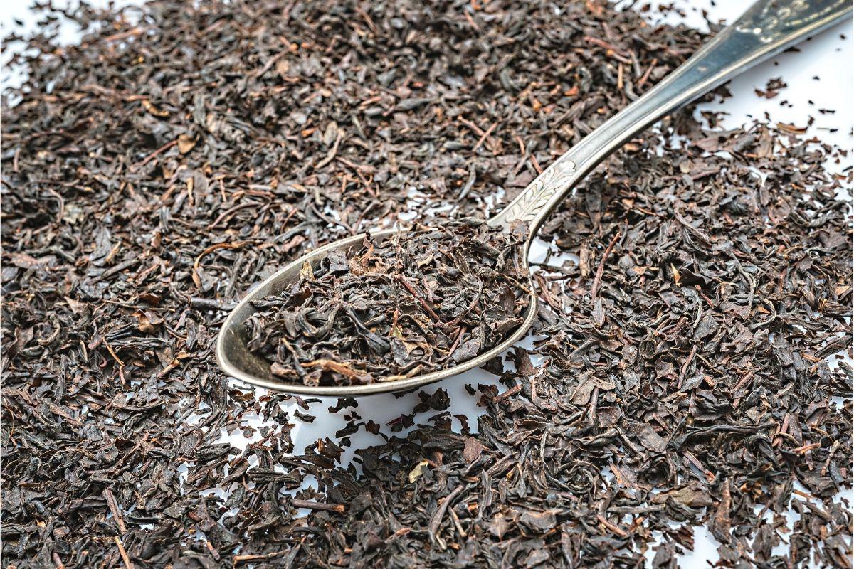 Blätter des schwarzen Tees auf Löffel
